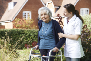 caregiver assisting an elderly woman